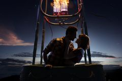 Young beautiful multiethnic couple kissing in the hot air balloon. night and sunrise around. Young beautiful multiethnic couple kissing in the hot air balloon royalty free stock image