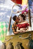Young beautiful multiethnic couple kissing in the hot air balloon. Very romantic picrure royalty free stock photos