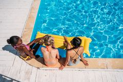 Young beautiful multiethnic women sitting near swimming pool. At resort royalty free stock photo