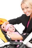 Young beautiful mum with baby in stroller. beautiful blond hugging toddler and smiling royalty free stock photos