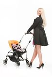 Young beautiful mum with baby in stroller. beautiful blond strolling toddler and smiling Royalty Free Stock Images