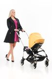 Young beautiful mum with baby in stroller. beautiful blond strolling toddler and smiling stock photo