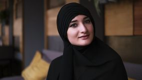Young beautiful muslim girl in black hijab is posing for the camera, watching at camera, blinking religious concept. Sitting in modern cafe. Blurred background stock video