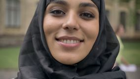 Young beautiful muslim girl in hijab turns her head to camera and smiling in daytime, in bad weather, religiuos concept stock video