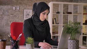 Young beautiful muslim girl in hijab is working with laptop in office, work concept, business concept, communication. Concept, religious concept stock video
