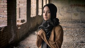 Young beautiful muslim woman in black hijab standing in abandoned building and looking at camera with scared and. Terrified expression stock video