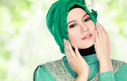 Young beautiful muslim woman with green costume wearing hijab Stock Photo