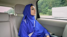 Young beautiful muslim woman in hijab sitting in car on passenger rear seat.  stock video footage