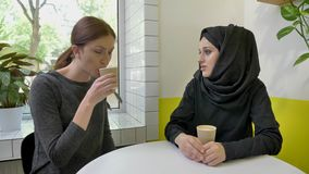 Young beautiful muslim woman in hijab telling something to other woman, drinking coffee, sitting in cafe.  stock video