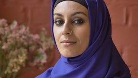 Young beautiful muslim woman in hijab turning and looking at camera, flowers and wall in background.  stock video footage