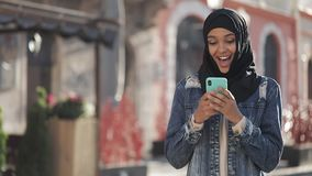 Young beautiful Muslim woman using smartphone standing on the old city background. She having good news on smartphone. Young beautiful Muslim woman using stock video