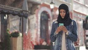Young beautiful Muslim woman using smartphone standing on the old city background. She having good news on smartphone. Young beautiful Muslim woman using stock video footage