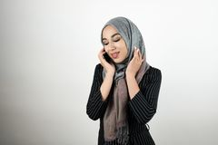 Young beautiful Muslim woman wearing turban hijab headscarf talking on the smartphone isolated white background royalty free stock photography