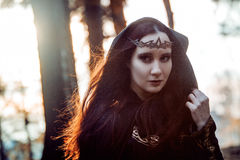 Young beautiful and mysterious woman in woods, in black cloak with hood, image of forest elf or witch. Young beautiful and mysterious woman in the woods, in a royalty free stock images