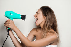 Young beautiful naked girl in towel singing with hairdryer. Royalty Free Stock Image