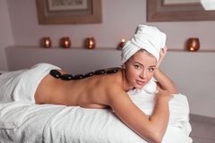 Young beautiful naked woman lying with black stones on her back in spa center royalty free stock photo
