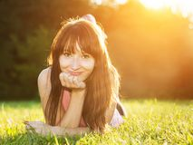 Young, beautiful, natural woman lying on the grass. At summer sunset, portrait. Happiness, fun and harmony stock photos