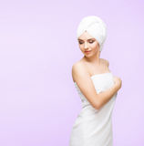 Young, beautiful and natural woman wrapped in towel isolated on. Young, beautiful and natural woman wrapped in over magenta background royalty free stock images