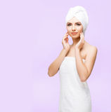 Young, beautiful and natural woman wrapped in towel isolated on. Young, beautiful and natural woman wrapped in over magenta background royalty free stock image
