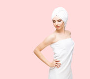 Young, beautiful and natural woman wrapped in towel isolated on. Young, beautiful and natural woman wrapped in towel over orange background royalty free stock photography