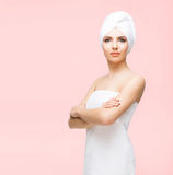 Young, beautiful and natural woman wrapped in towel isolated on. Young, beautiful and natural woman wrapped in towel over orange background royalty free stock photo