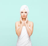 Young, beautiful and natural woman wrapped in towel isolated on. Young, beautiful and natural woman wrapped in towel over cyan background royalty free stock images