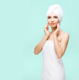 Young, beautiful and natural woman wrapped in towel on. Young, beautiful and natural woman wrapped in towel over cyan background royalty free stock photo