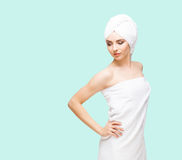 Young, beautiful and natural woman wrapped in towel isolated on. Young, beautiful and natural woman wrapped in towel over cyan background royalty free stock photo