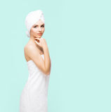 Young, beautiful and natural woman wrapped in towel on. Young, beautiful and natural woman wrapped in towel over cyan background stock image