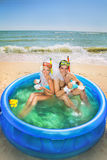 Newly-married couple enjoying on the beach. A young and beautiful newly-married couple enjoying on the beach in swimming pool with cups of coffee Royalty Free Stock Photo