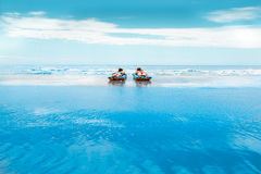 A young and beautiful newly-married couple enjoying on an inflat. Able mattress on a beach closed blue maldivian sea Royalty Free Stock Photos
