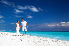 Young  beautiful newlyweds on white sandy beach Stock Images