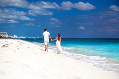Young beautiful newlyweds on white sandy beach, rear view Royalty Free Stock Images