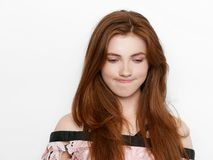 Young beautiful excited lady with gorgeous natural red hair, blank copy space on white background for advertisement or promotiona stock photography