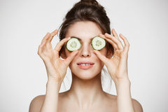 Young beautiful nude girl smiling hiding eyes behind cucumber slices over white background. Beauty skincare and. Cosmetology. Copy space Stock Image