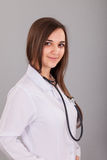 Young and beautiful nurse on a grey Stock Images