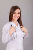 Young and beautiful nurse on a grey Royalty Free Stock Image