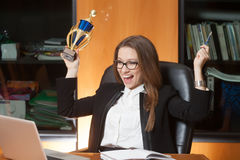 Young beautiful office lady winner. Young beautiful woman sitting on the black leather chair and happy for win Stock Images