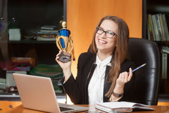 Young beautiful office lady winner. Young beautiful woman sitting on the black leather chair and happy for win Stock Photography