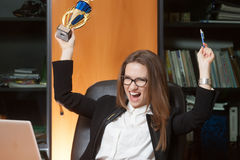 Young beautiful office lady winner. Young beautiful woman sitting on the black leather chair and happy for win Stock Photo