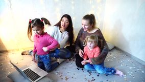 Older women spend time together with younger girl children and sisters using laptop and sitting on floor on background. Young and beautiful older girls together stock video footage