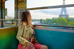 Young beautiful Parisian woman in subway. Young beautiful Parisian woman travelling in a subway train, sitting near the window and looking at the Eiffel tower Royalty Free Stock Photography