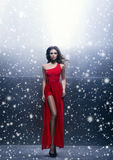 Young, beautiful and passionate woman in a wavy, long, red dress. Over winter background royalty free stock photography