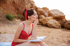 Young beautiful pensive pin up girl sitting with book Stock Image