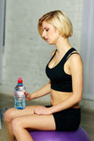 Young beautiful pensive woman with bottle of water Stock Photography