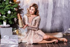 Young beautiful pensive woman sitting on floor near christmas tree with closed eyes. Pretty girl in evening dress posing in stock photo