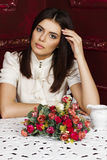 Young beautiful pensive woman sitting at the table Stock Photos