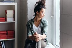 Free Young Beautiful Pensive Woman With Dark Curly Hair Sitting On Window Sill In Audience Of University Thoughtfully Looking Stock Photo - 183930330
