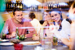 Young beautiful people with cocktails in bar or club Royalty Free Stock Image