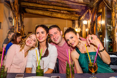 Young beautiful people with cocktails in bar or club Royalty Free Stock Photo